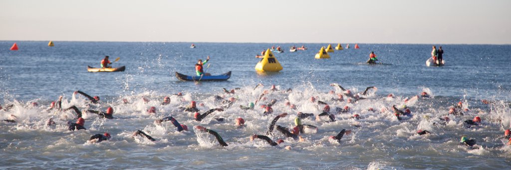 IRONMAN 70.3 Turkey athletes swimming in the crystal-clear water of Turkish Riviera while volunteers in canoes are watching them