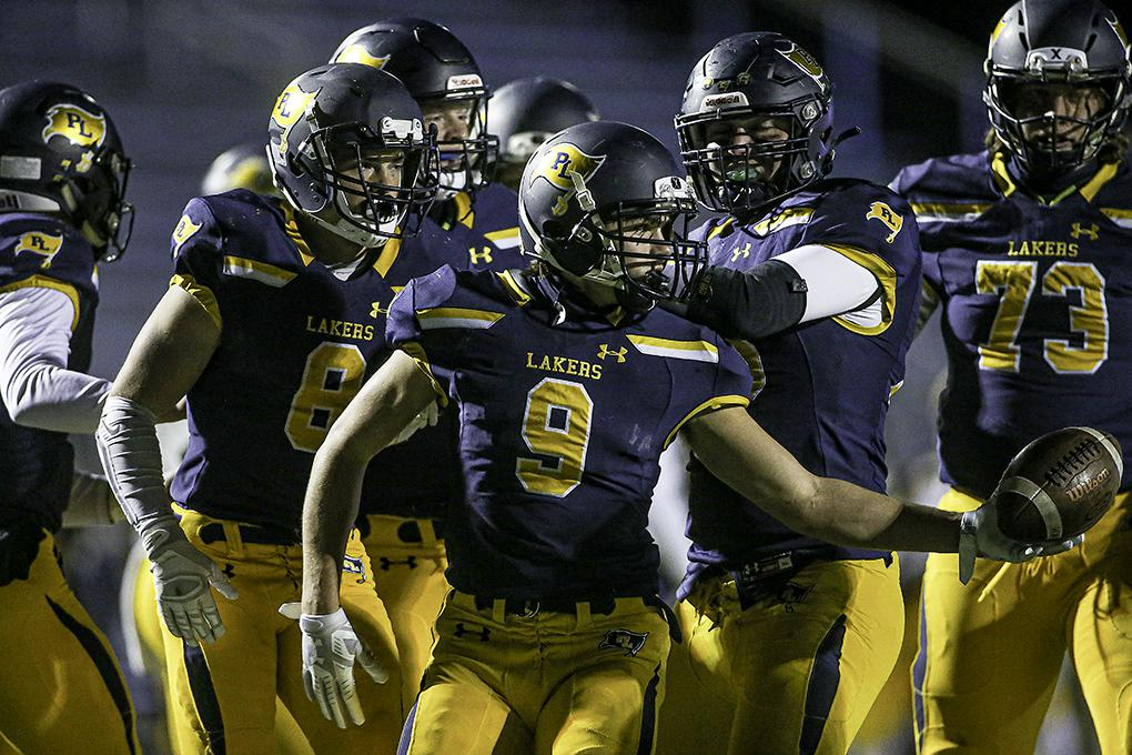 Prior Lake running back Tanner Newlin (9) handed the ball to an official as his teammates celebrated his first-half touchdown run. Photo by Mark Hvidsten, SportsEngine