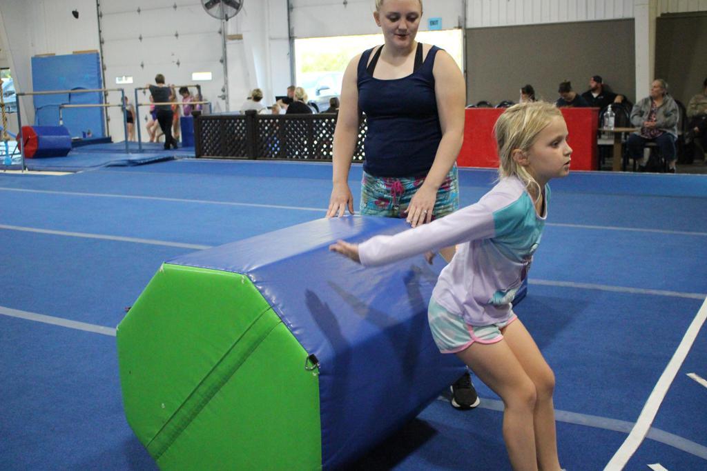 Cheerleader learning a back handspring