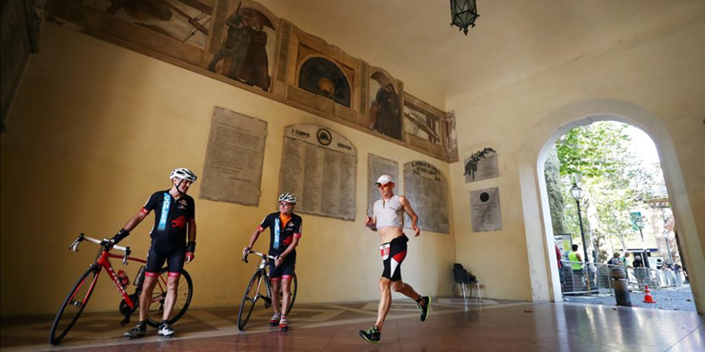Two triathletes with bikes, one triathlete running