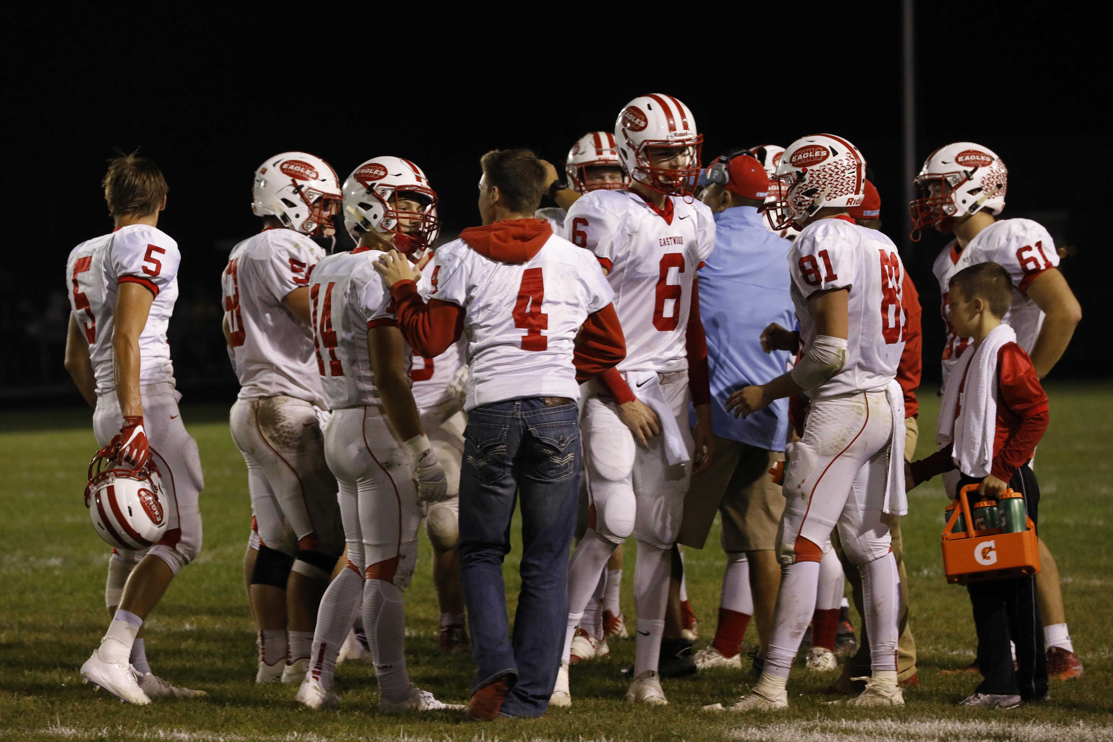 Eastwood senior Cade Boos (4) hopped out on one foot to talk with teammate Alex Ross (14) in the huddle during the game vs. Otsego THE BLADE/KATIE RAUSCH