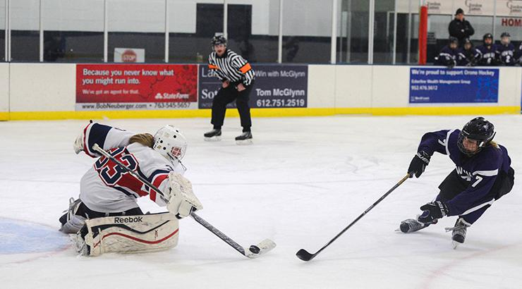 Orono goaltender Anna Lisle (33) pushes the puck away from New Ulm forward Dani Weiss (7). Lisle had 29 saves in the 2-2 tie. Photo by Carter Jones, SportsEngine