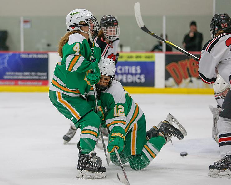 Edina teammates Olivia Swaim (4) and Lolita Fidler (12) collided in a rush on the Eden Prairie net late in the third period. Edina scored twice in the final minutes to secure a 3-1 victory. Photo by Mark Hvidsten, SportsEngine