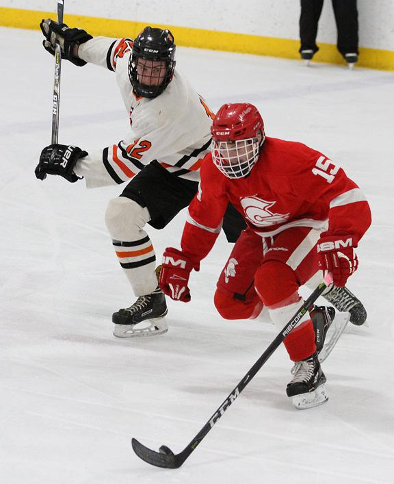 BSM junior forward Ian Bahr skates through the neutral zone with St. Louis Park defenseman Shea Pekarek in pursuit during the first period. Photo by Drew Herron, SportsEngine