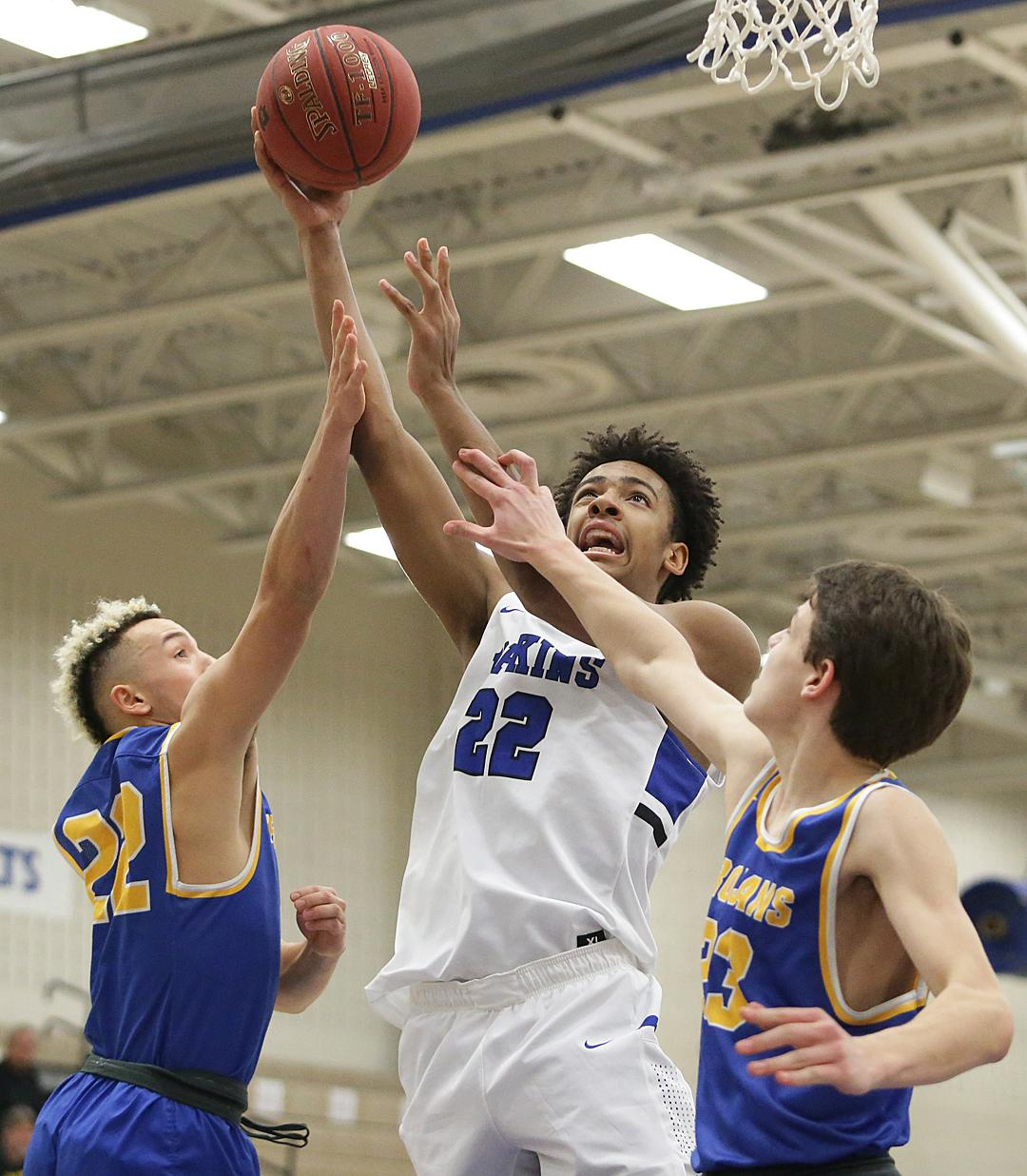 Zeke Nnaji (22) pushes thru Wayzata defenders Kody Williams (22) and Camden Heide (23). Nnaji scored a game-high 23 points leading the Royals to a 89-63 to remain undefeated in the Lake Conference. Photo by Cheryl Myers, Courtesy of Hopkins Boys Basketbal
