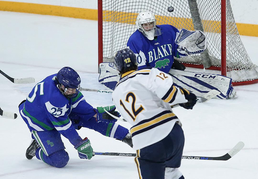 Tyler Dingmann (12) sends the puck flying past goaltender Aksel Reid to give the Trojans a three goal lead after two periods. Wayzata advances to the section semifinals on Saturday. Photo by Cheryl Myers, SportsEngine