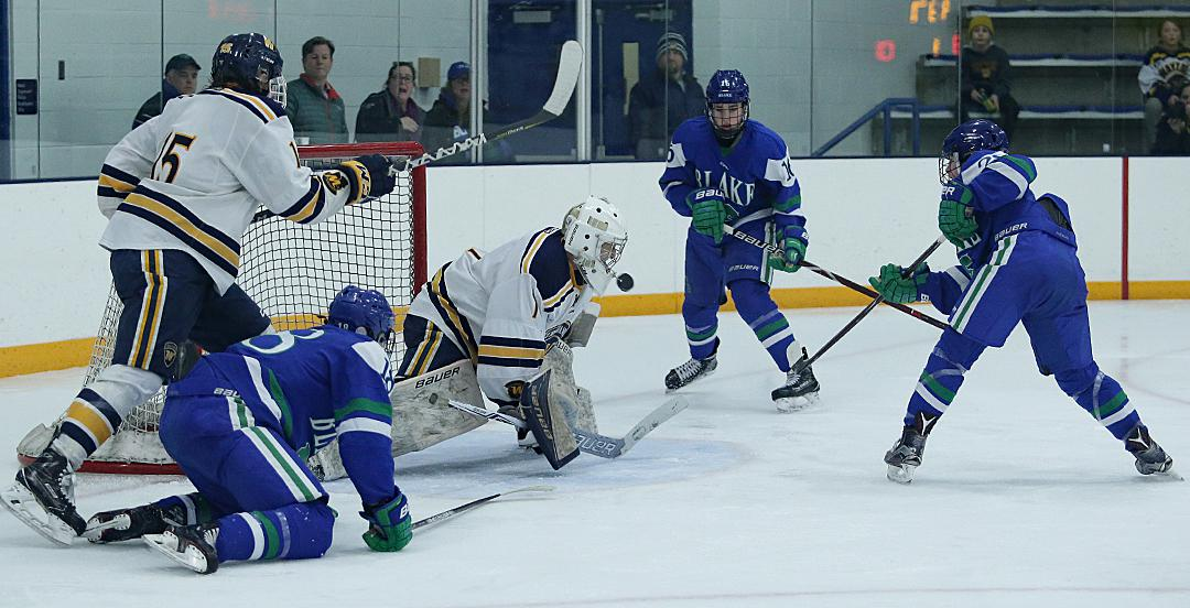 Freshman forward Joe Miller (far right) lifts the puck up and over Wayzata goalie Trevor Wong for his first of two goals in the third period cutting Wayzata's lead to one. Photo by Cheryl Myers, SportsEngine