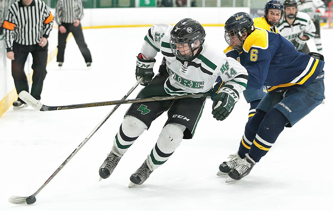 Joe Simon (14) works the puck around Prior Lake defender Ty Trachsel (6). Holy Family eased past Prior Lake 5-2 in the Section 2 Class 2A semifinal match up at Braemar arena. Photo by Cheryl Myers, SportsEngine