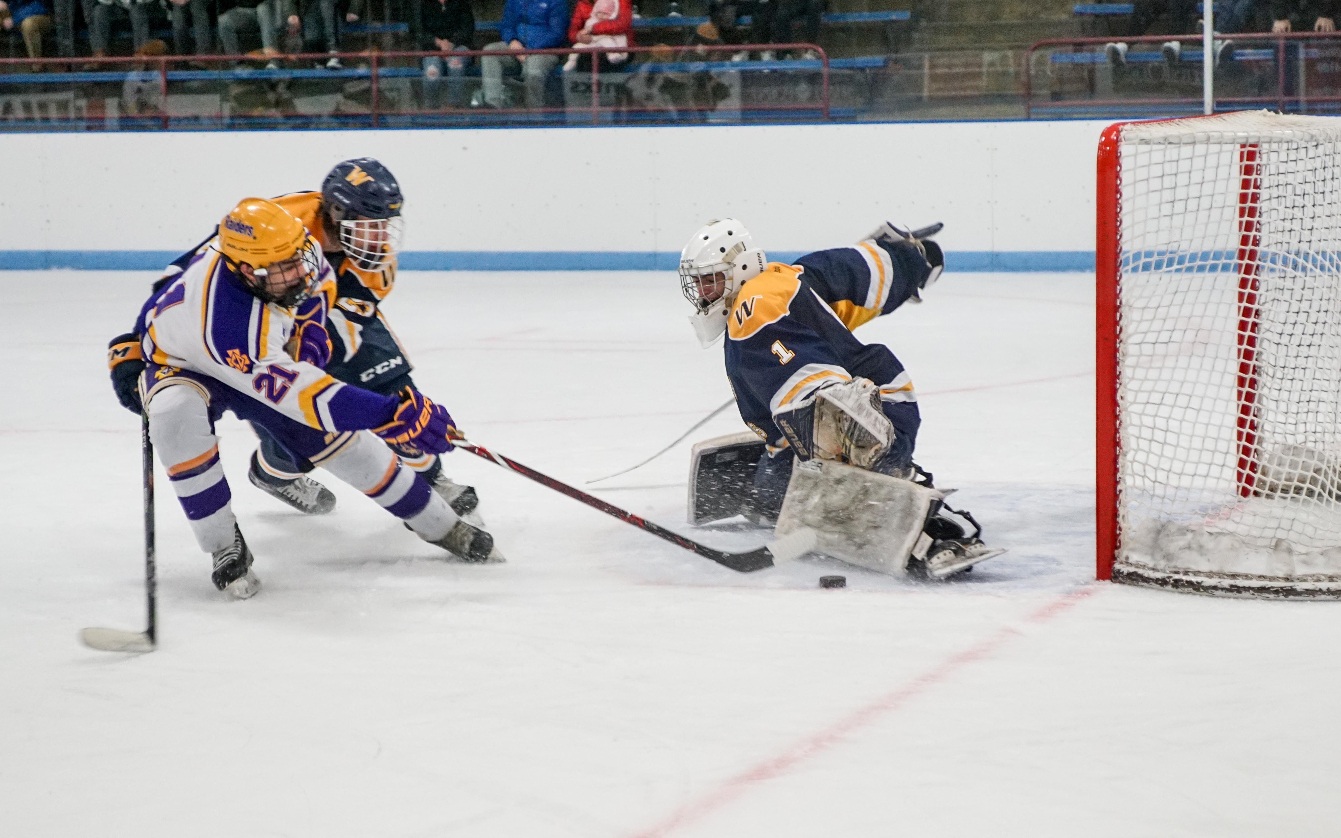 Wayzata goalie Trevor Wong stops Cretin-Derham Hall's Joe Buckingham (21) from scoring with a minute remaining in the game, helping the Trojans escape with a 3-2 victory in a Class 2A, Section 6 semifinal on Feb 24. Photo by Korey McDermott, SportsEngine