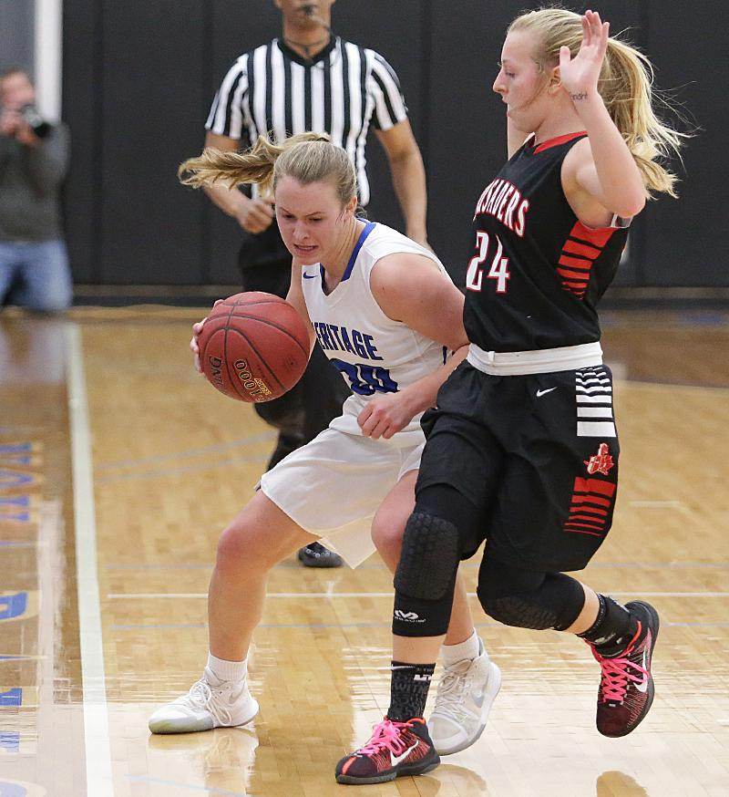 Taylie Scott (20) works her way down the sideline defender Nicole Klaustermeier (24) drawing a foul late in the game. Scott had a game high 27 points in a 71-58 win for Heritage Christian earning their first state tournament berth. Photo by Cheryl Myers,