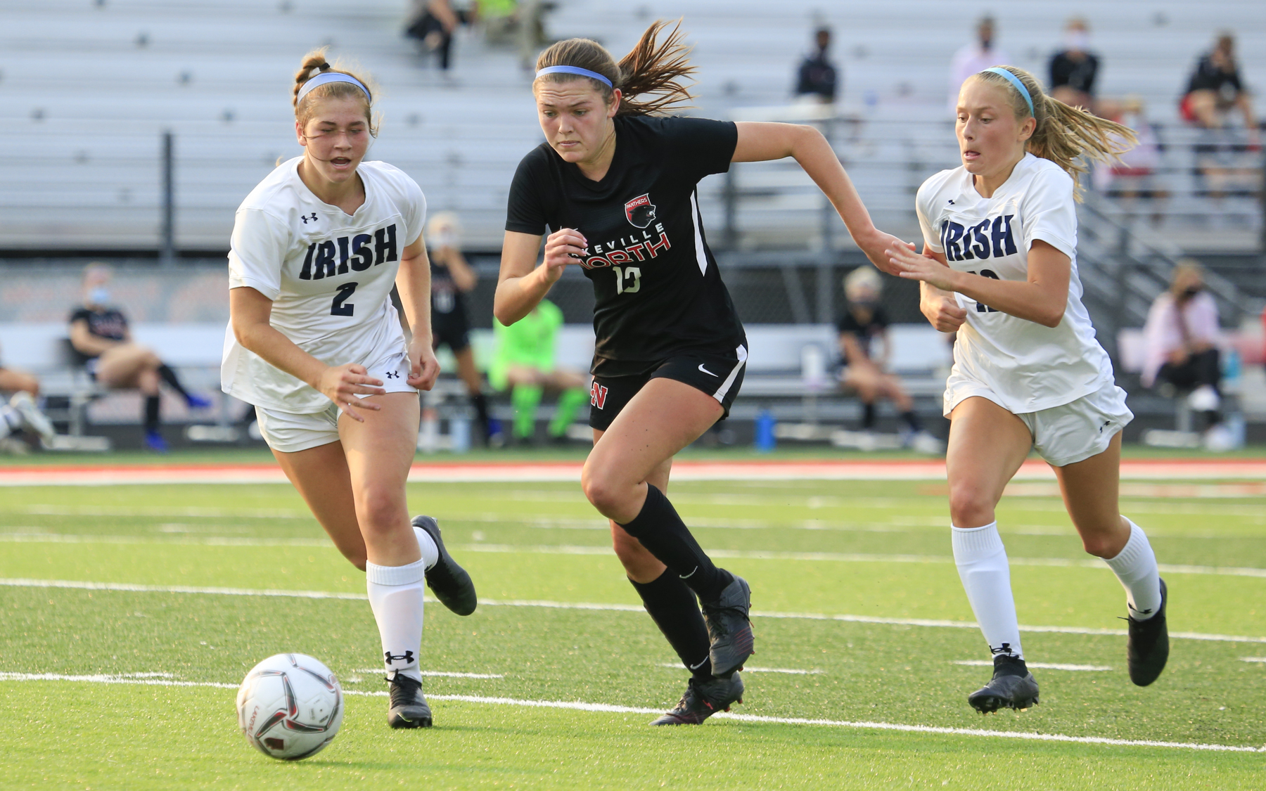 Lakeville North's Abby Ruhland (13) attempts to outrun Rosemount's Joey Edgar (left) and Ashley Herold (right) during Tuesday evening's game. The Panthers and Irish played to a 0-0 draw at Lakeville North High School. Photo by Jeff Lawler, SportsEngine