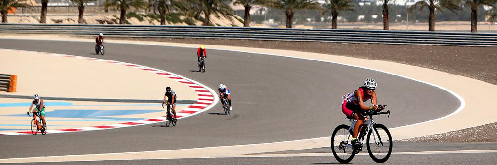 Athletes are biking through the for motorsport used venue Bahrain International Circuit which is lined with palm trees and sand