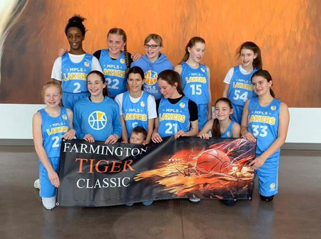 Mpls Lakers Youth Traveling Basketball Program Inc Girls 7th Grade Gold pose with the tournament banner after winning the Consolation Bracket at the Farmington Girls Tiger Classic tournament in Farmington, MN