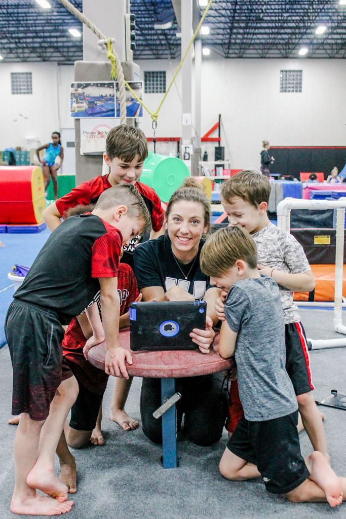 Coach giving boys gymnastics lesson