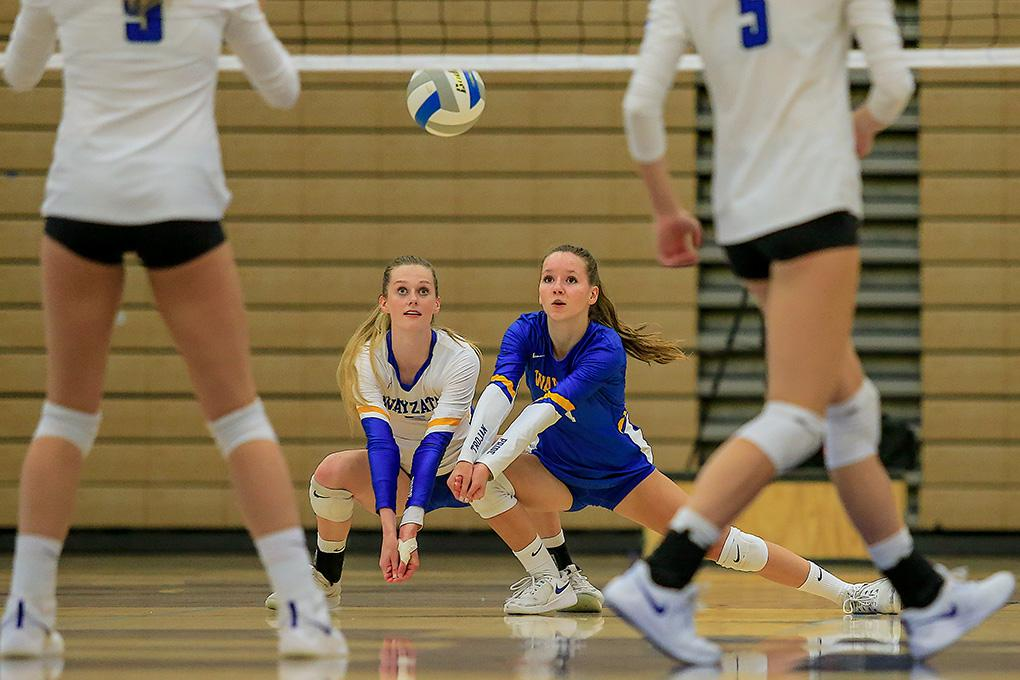 Wayzata's Ella Voegele (right) and Avery Seesz prepare to field a serve. Photo by Mark Hvidsten, SportsEngine