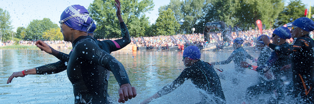 IRONMAN 70.3 Kraichgau athletes are running into Hardtsee with huge crowds watching from behind in the early morning