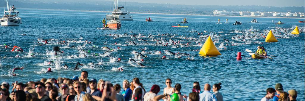 Athletes swimming behind each other in the sea in Alcudia at IRONMAN Mallorca