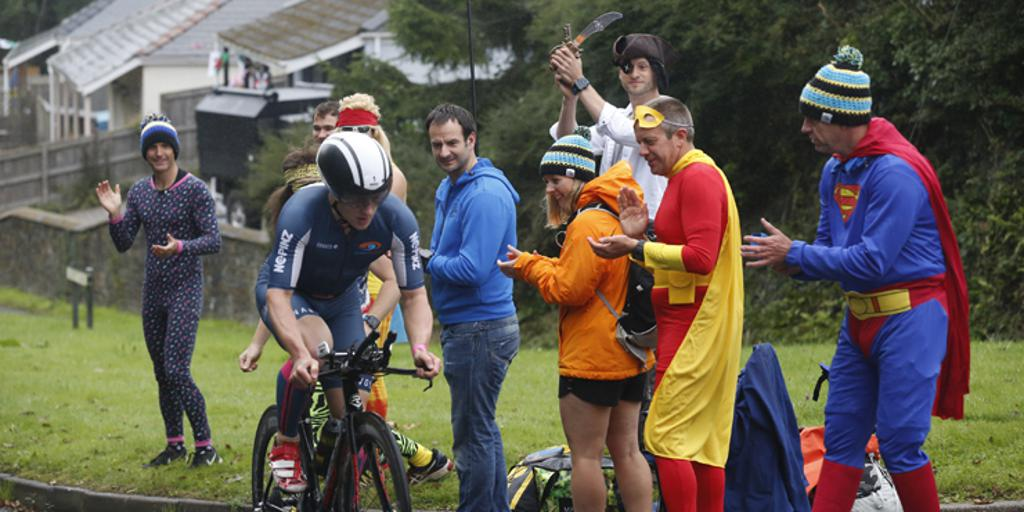 Supporters cheering on a triathlete biking uphill