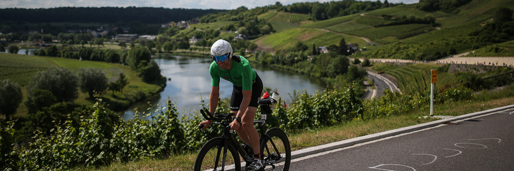 A smiling athlete biking through the heart of the region with vineyards left and right at IRONMAN 70.3 Luxembourg