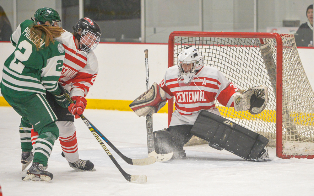 Holy Family Catholic senior forward Sydney Paulsen takes a shot on goal against Centennial goaltender Anna Gilgosch. The Fire defeated the Cougars 3-0 Thursday night. Photo by Earl J. Ebensteiner, SportsEngine