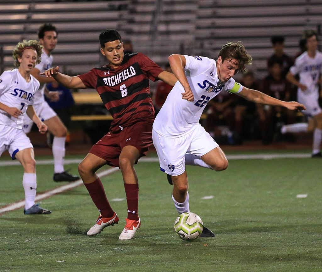 Junior forward Carter Hermanson (22) steals the ball away from Osvaldo Avila Rodriguez (6) at midfield. Hermanson leads Holy Angels in scoring with six goals and two assists. Photo by Cheryl A. Myers, SportsEngine