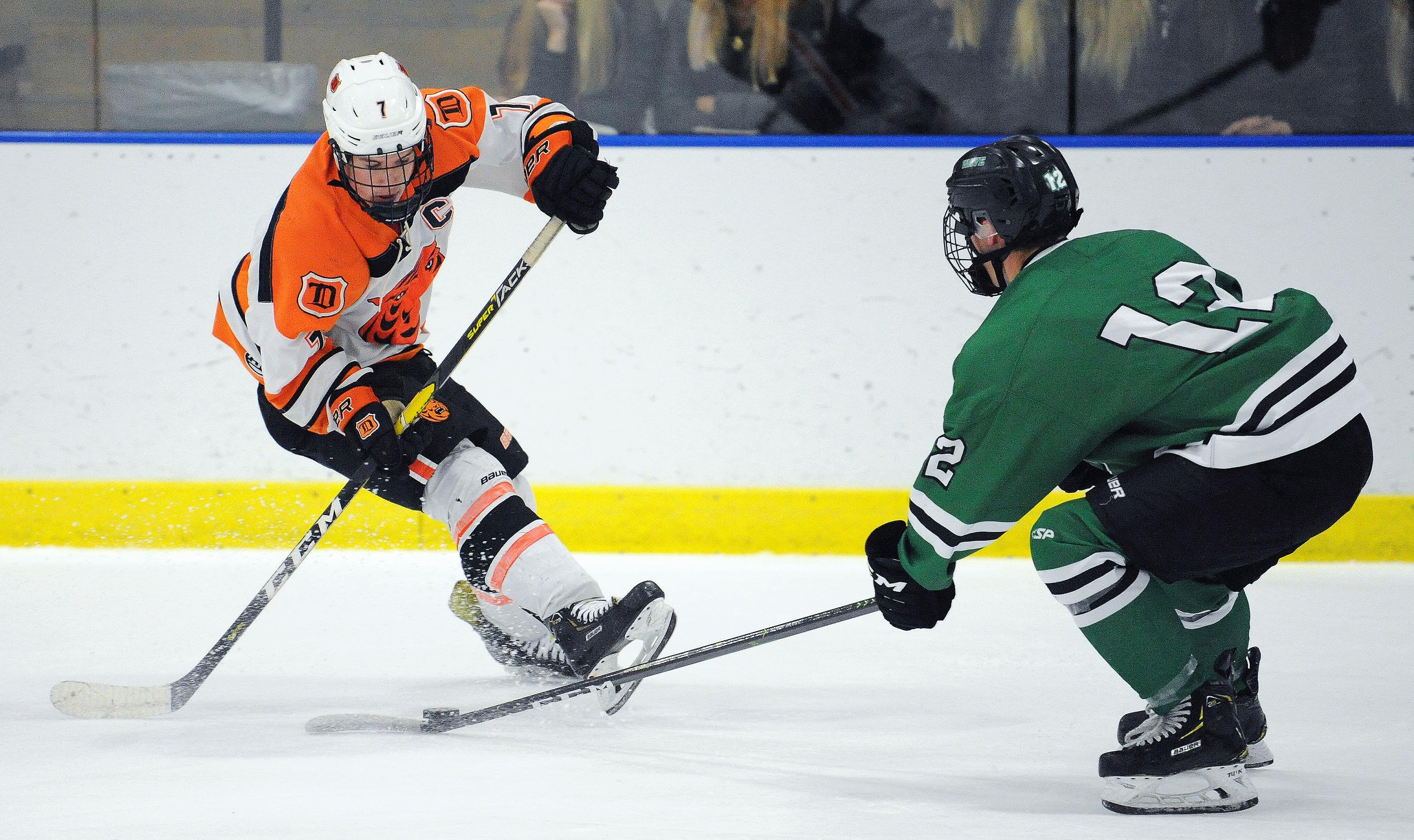 Delano senior Kory Dunnigan attempts to work his way past East Grand Forks defenseman Josh Nelson on Saturday in Delano. Photo by Loren Nelson, LegacyHockeyPhotography.com