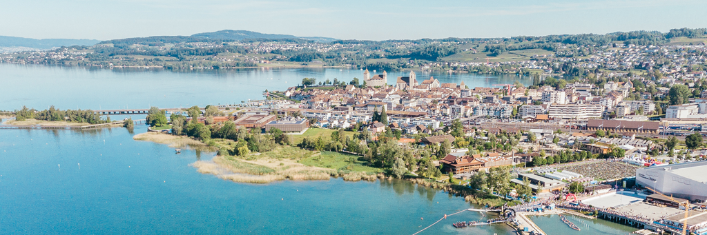 City of Rapperswil-Jona surrounded by Obersee and green hills on a sunny day in Switzerland