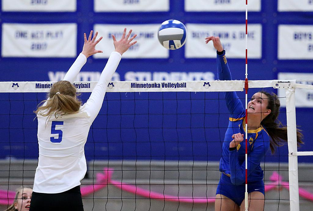 Outside hitter Kate Long (right) sends the ball past Alison Sundem (5).  The Trojans lost in three sets to the Skippers at Minnetonka High School. Photo by Cheryl Myers, SportsEngine