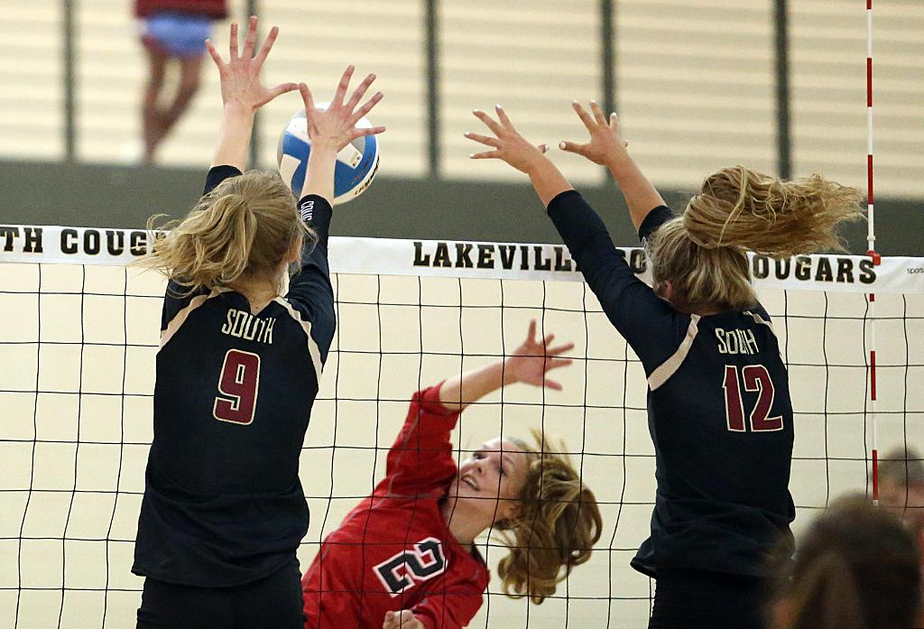Lakeville South's Nicole Banitt (9) and Jasmine Weidemann (12) go up for the block against Maddy Hornyak (2). The Cougars prevailed in the crosstown rivalry match up with a 3-2 victory over the Panthers. Photo by Cheryl Myers, SportsEngine