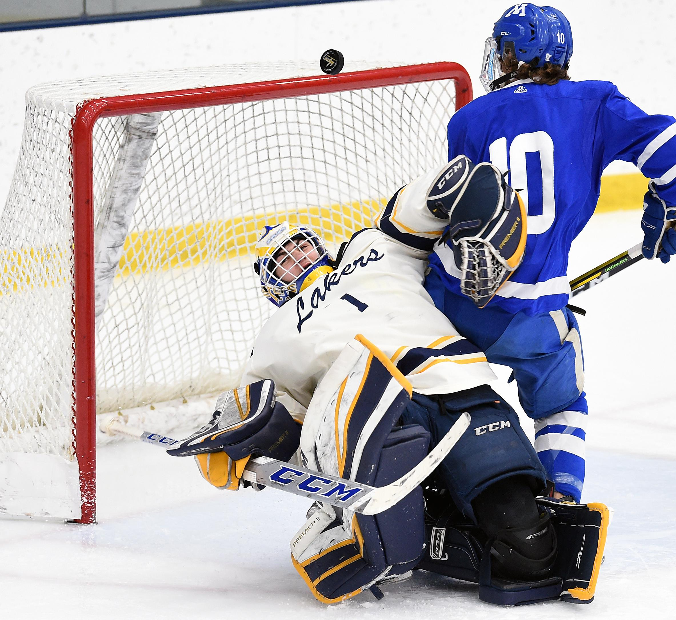 Minnetonka's Hunter Newhouse gets tangled with Prior Lake goaltender Trevor Boschee as the puck drops into the net for a third-period goal. The Skippers defeated the Lakers 3-1 on Saturday. Photo by Loren Nelson, SportsEngine