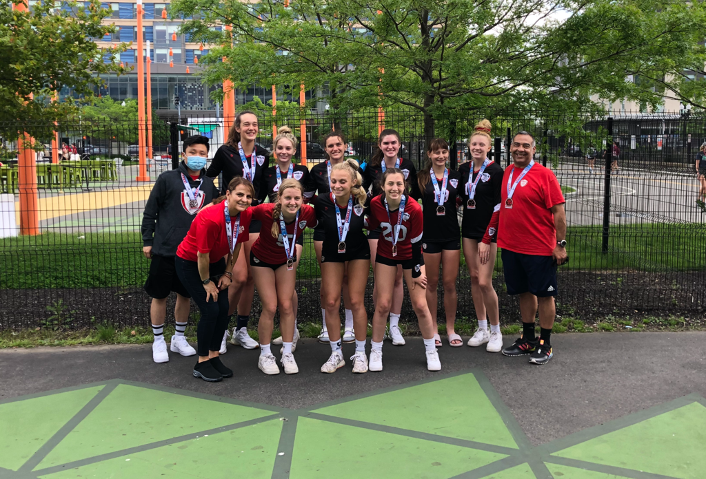 Girls volleyball team and coaches with medals around their necks