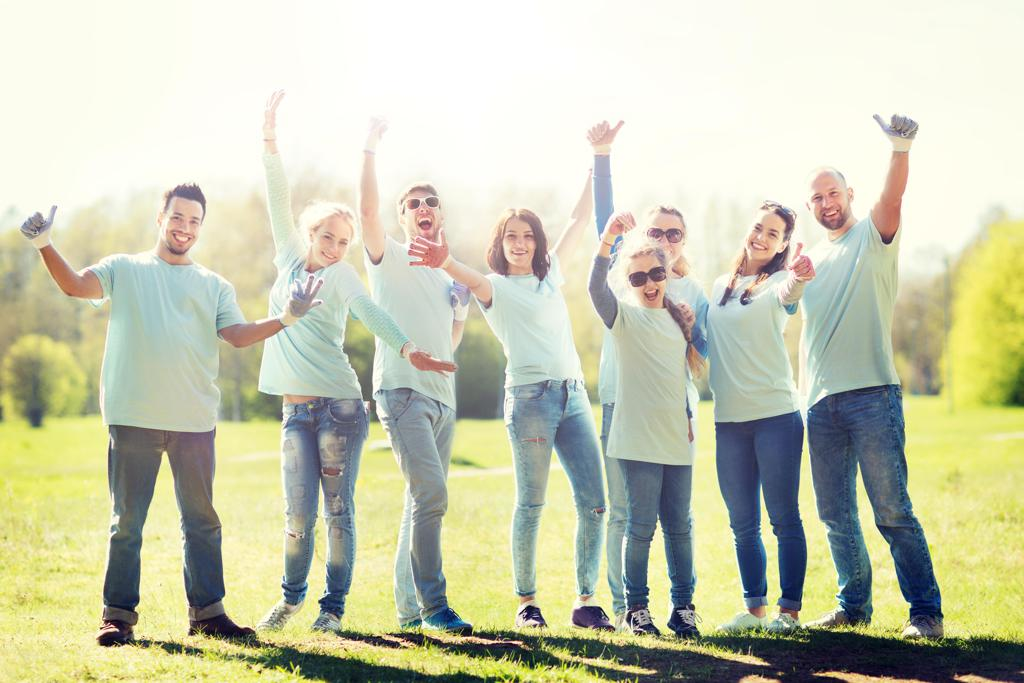 Group of people happy after volunteering in light blue shirts and garden gloves on holding their hands in the air in joy