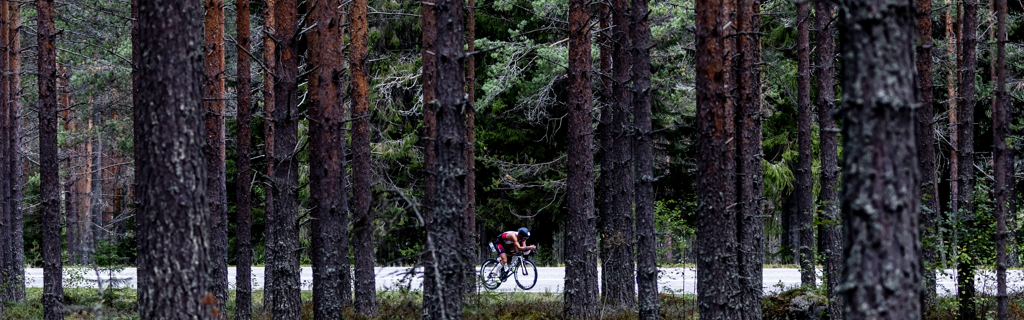 Athlete biking on the street surrounded by woods in Kuopio-Tahko Finland