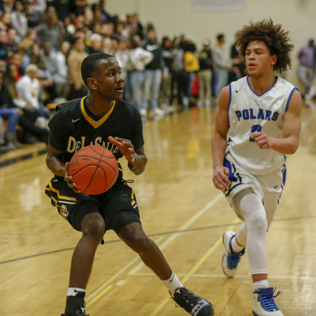 DeLaSalle senior Kameron Givens pulls up for a shot as Minneapolis North's Eli Campbell defends. Givens had 20 points in the Islanders' victory Tuesday night over the Polars. Photo by Jeff Lawler, SportsEngine
