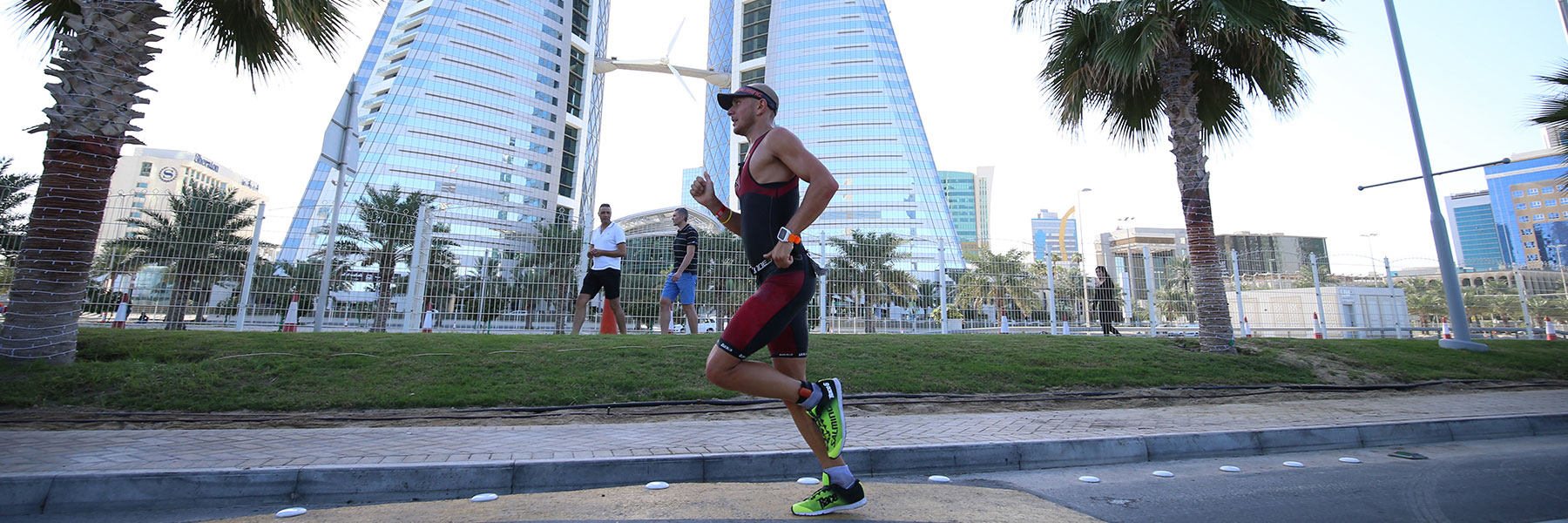 Single athlete passing by Bahrain World Trade Center while running along King Faisal Highway at IRONMAN 70.3 Bahrain