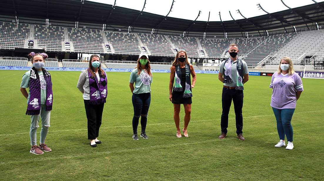 Members of the Lavender Legion and LouCity ladies with Christie Pearce Rampone, left, fiance of Racing Louisville FC coach Christy Holly, right. EM Dash Photography
