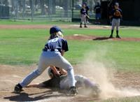 Players sliding into plate and attempting to be tagged out