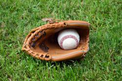 Tan leather baseball glove and ball laying on green grass