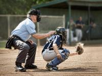 Cather and umpire with dust coming from catchers glove after a catch