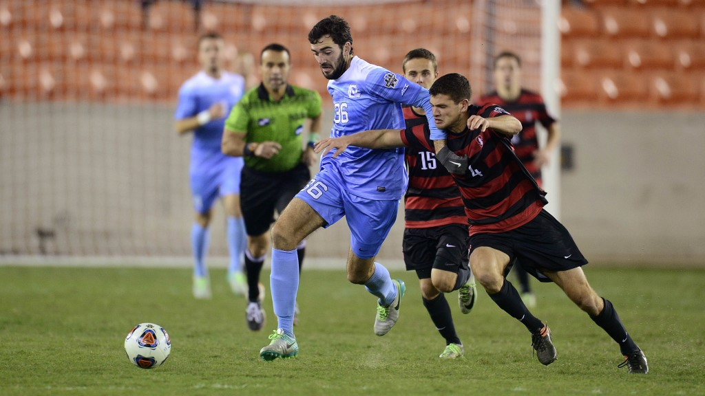 Tucker Hume, in a game, while playing for Tar Heels jersey, battling for possession against two defenders