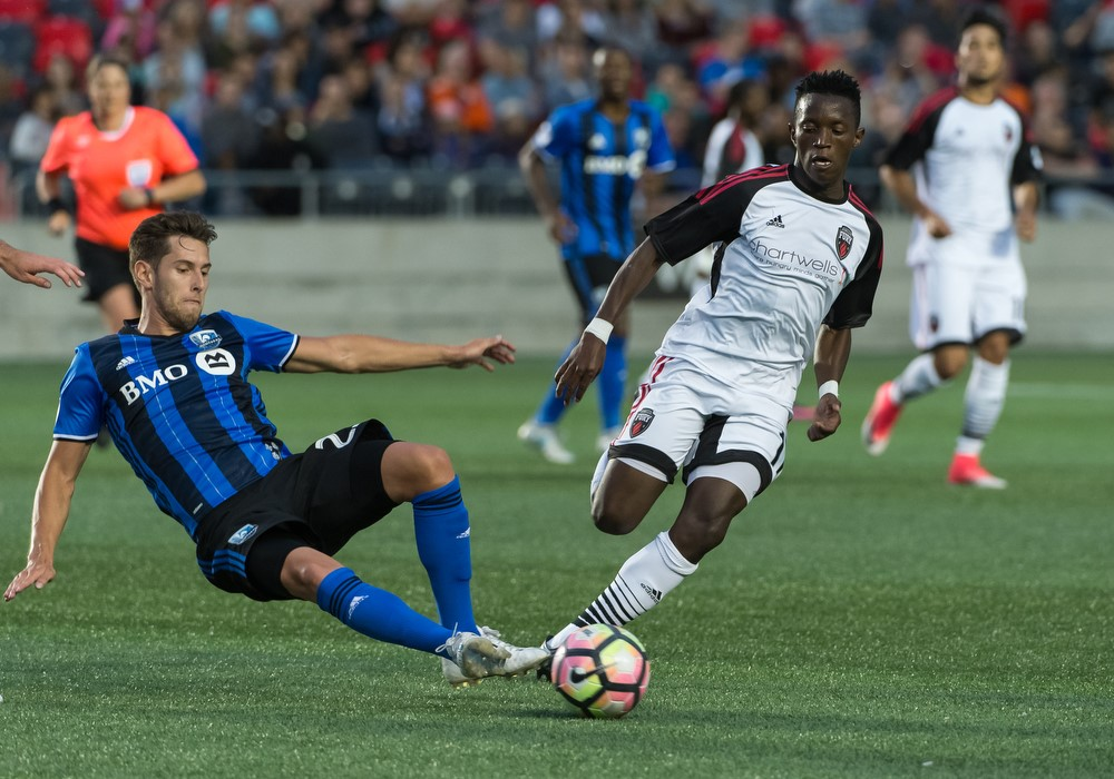 Azake Luboyera trying to avoid a tackle against a Montreal Impact player