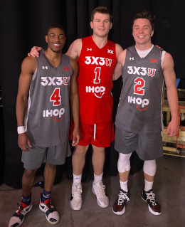 Three basketball players stand smiling at the camera