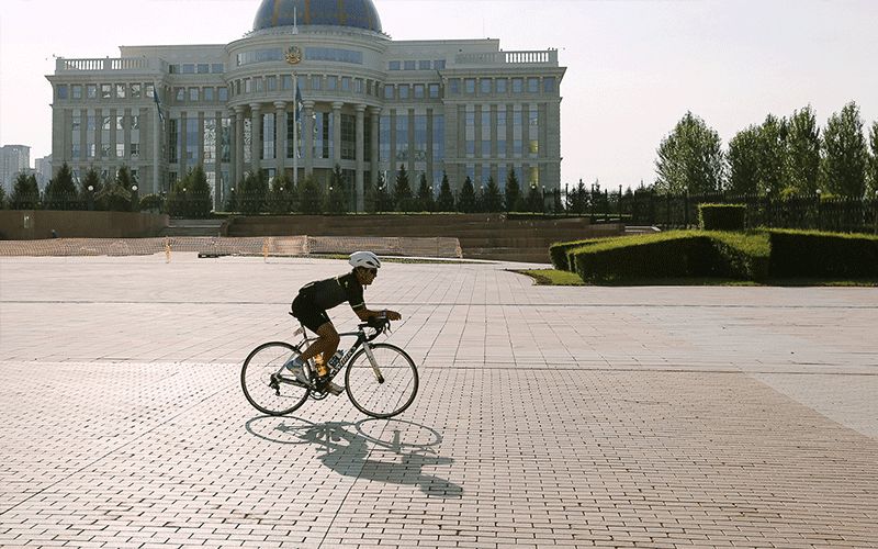 IRONMAN Kazakhstan Support - Picture of an athlete biking on a town square