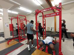 Rugby players lifting weights in weight room